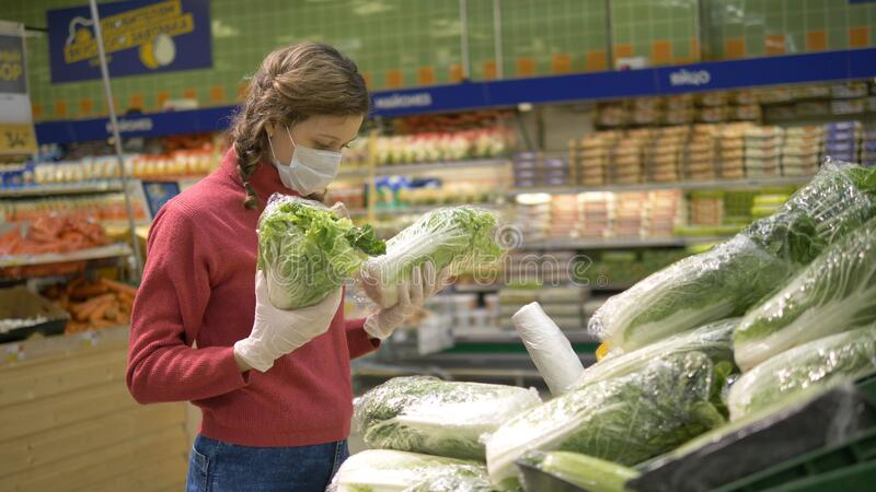 Girl in mask and gloves chooses fresh cabbage vegetables in supermarket, quarantine coronavirus covid-19. Young girl in a protective mask and gloves chooses stock photos