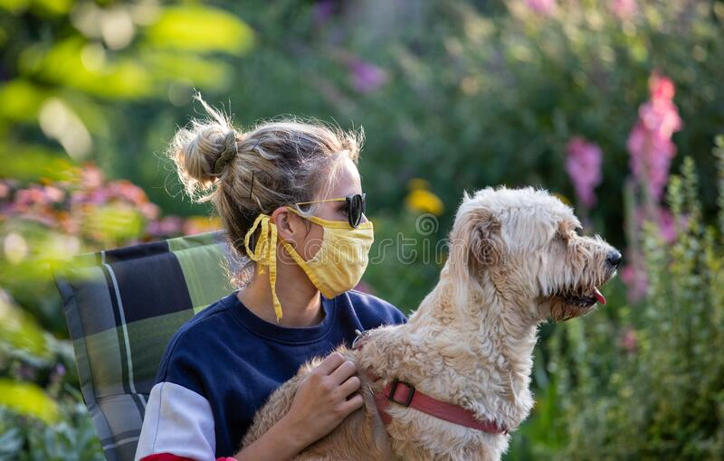 Girl with mask holding dog on lap in garden royalty free stock image