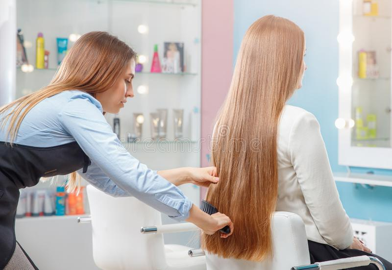 Girl master of Spa care combs long dark hair client sitting on chair. In beauty salon royalty free stock photo