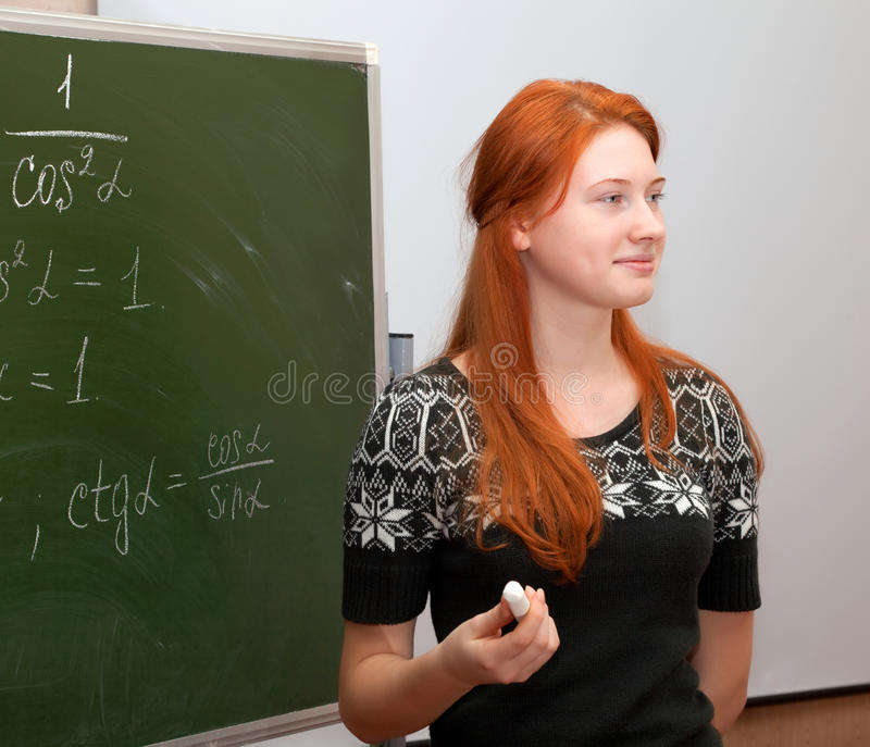 Girl in math class. Writing formulas on a blackboard royalty free stock photos
