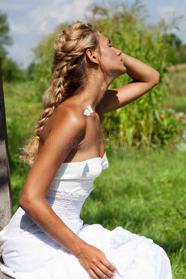 Girl on the meadow in summer day stock photo