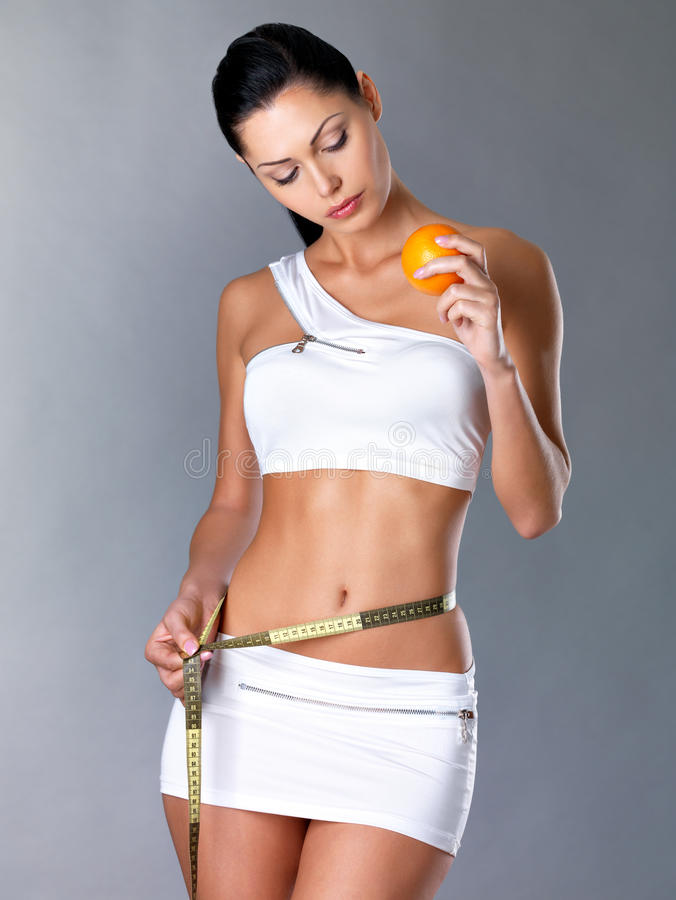 Download Girl Measures Figure And Holding Orange Stock Image - Image: 27654967