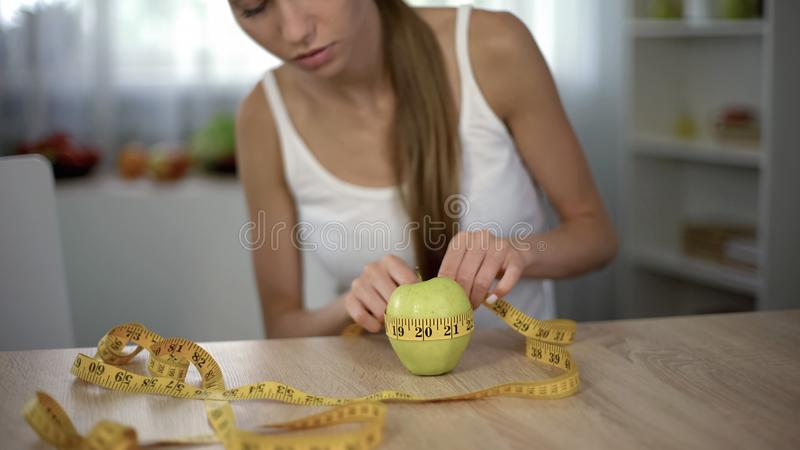 Girl measuring apple with tape line, counting calories, organic food and diet royalty free stock image