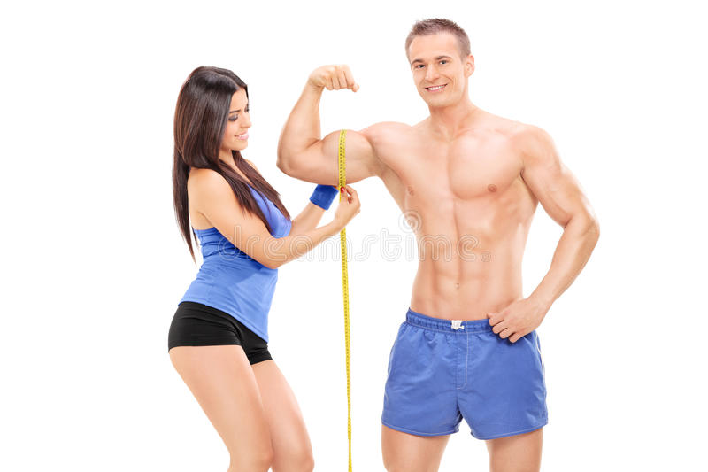 Girl measuring a bicep of a young male athlete royalty free stock images