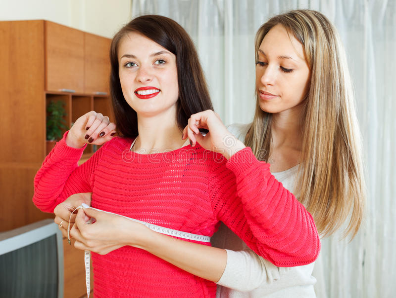 Girl measuring  bust of girlfriend with measuring tape