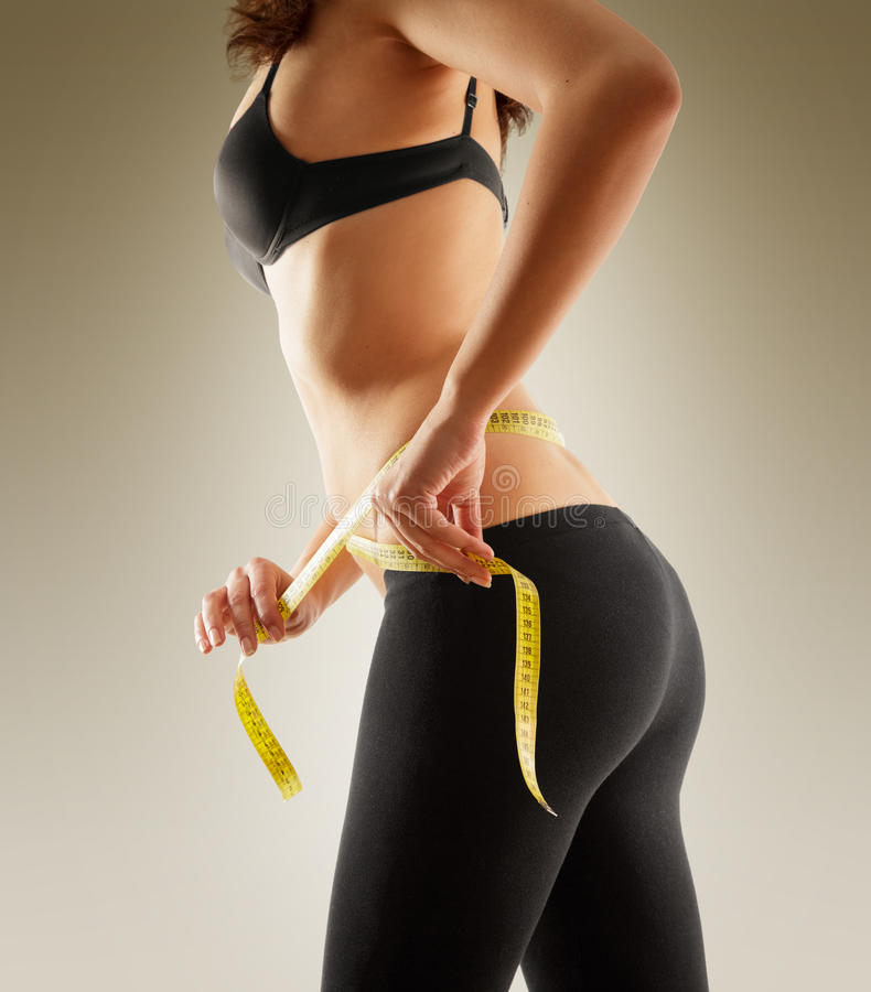 Girl measuring her waist with tape measure royalty free stock image