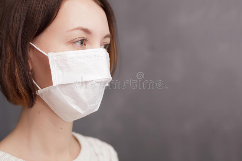 Girl in medical disposable mask looking at the camera. royalty free stock photos