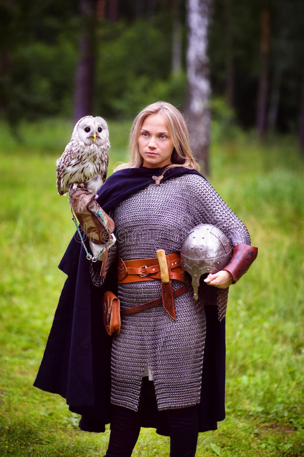 Girl in medieval armor, holding an owl royalty free stock photo