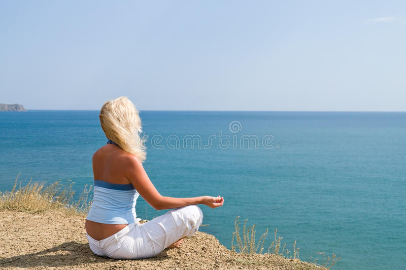 Girl meditating in the lotus position. On the background of the sea stock photos