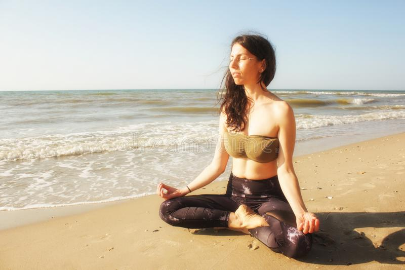 Girl meditating in lotus yoga on coast of sea on the beach. Young beautiful healthy woman making meditation on the beach, sunrise royalty free stock images