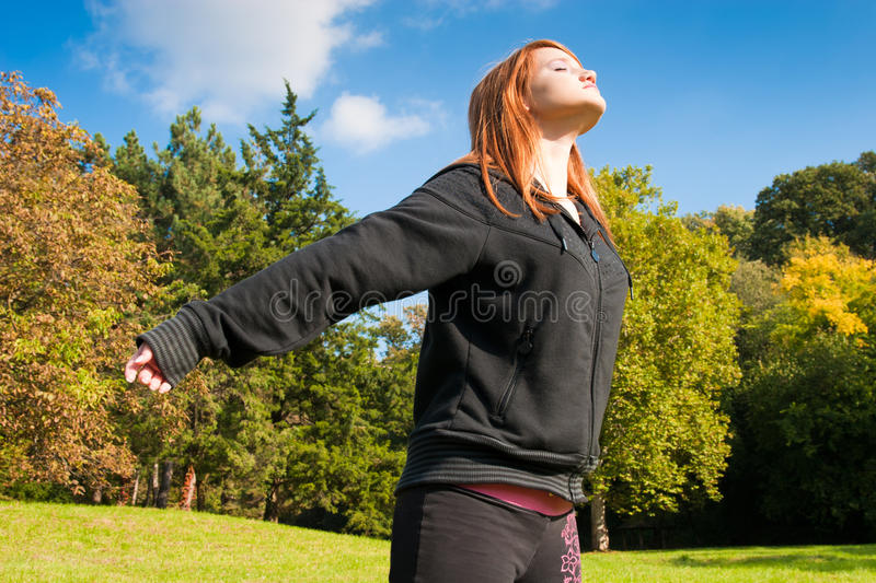 Girl meditating in nature. Beautiful red-haired girl meditating in nature stock photos