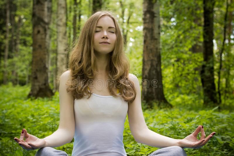 A girl is meditating in nature. A blonde meditates in the forest in a lotus position royalty free stock photography