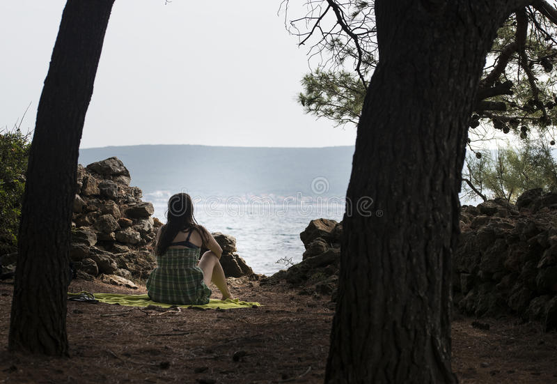Girl is meditating and resting at sea. Girl is meditating and resting at sea bellow pinaceae trees stock images