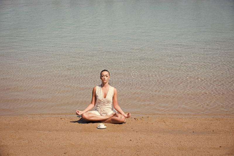 Girl meditating in yoga pose with coffee cup at water royalty free stock photography