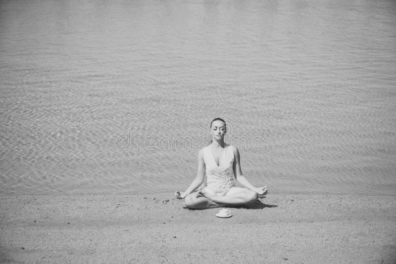 Girl meditating in yoga pose with coffee cup at water stock photography