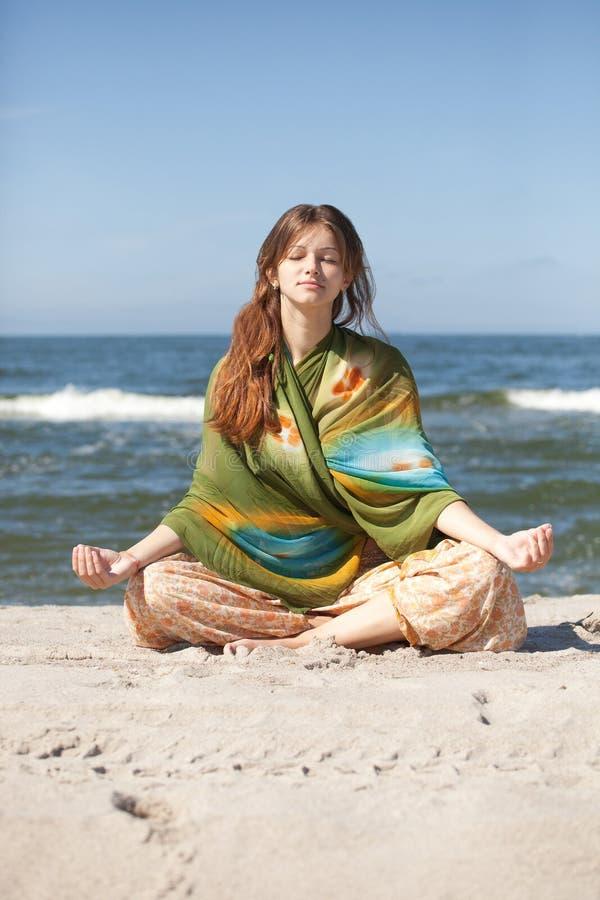 Girl meditating. Young beautiful girl meditating on beach in lotus position stock photo