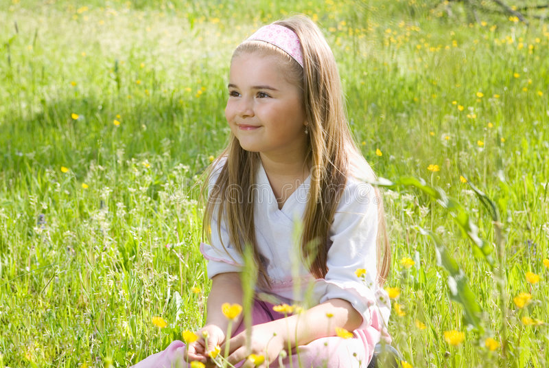 Girl in the medow. Little girl sitting at the medow in the grass in spring or summer royalty free stock photos