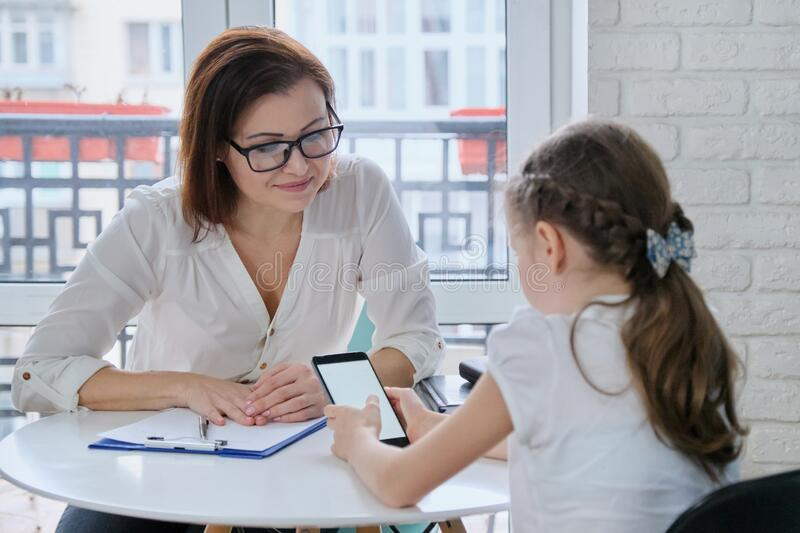 Girl at meeting with psychologist showing his social page on smartphone. Talking psychiatrist and child, mental health of children stock photo