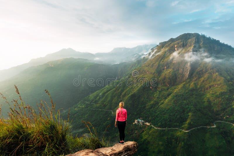 Girl meets sunrise in the mountains. Girl traveling to Sri Lanka. Mountain sports. Athlete happy finish. Mountain tourism royalty free stock photo