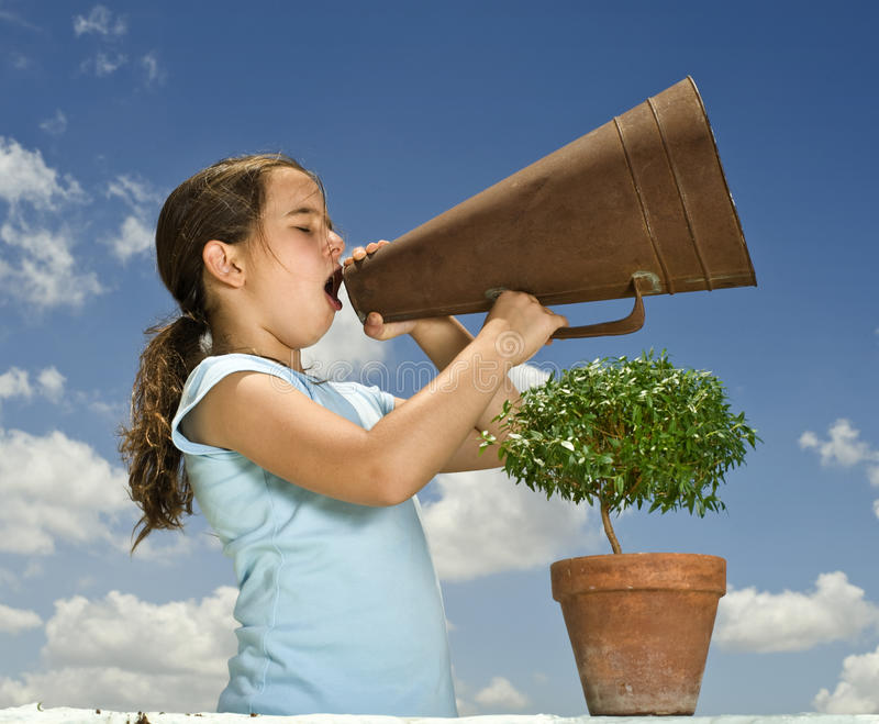 Girl with megaphone and small tree. Young girl holding and small tree and shouting with a megaphone against blue sky royalty free stock images