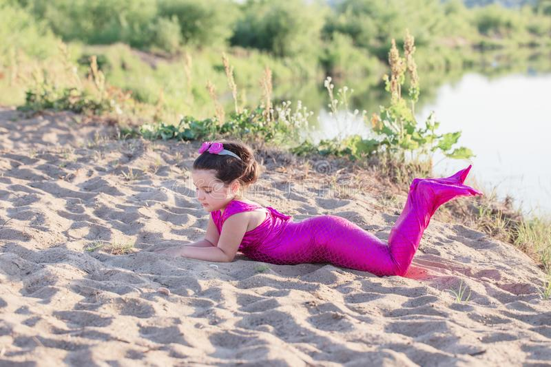 Girl in mermaid costume on the lake shore stock photography