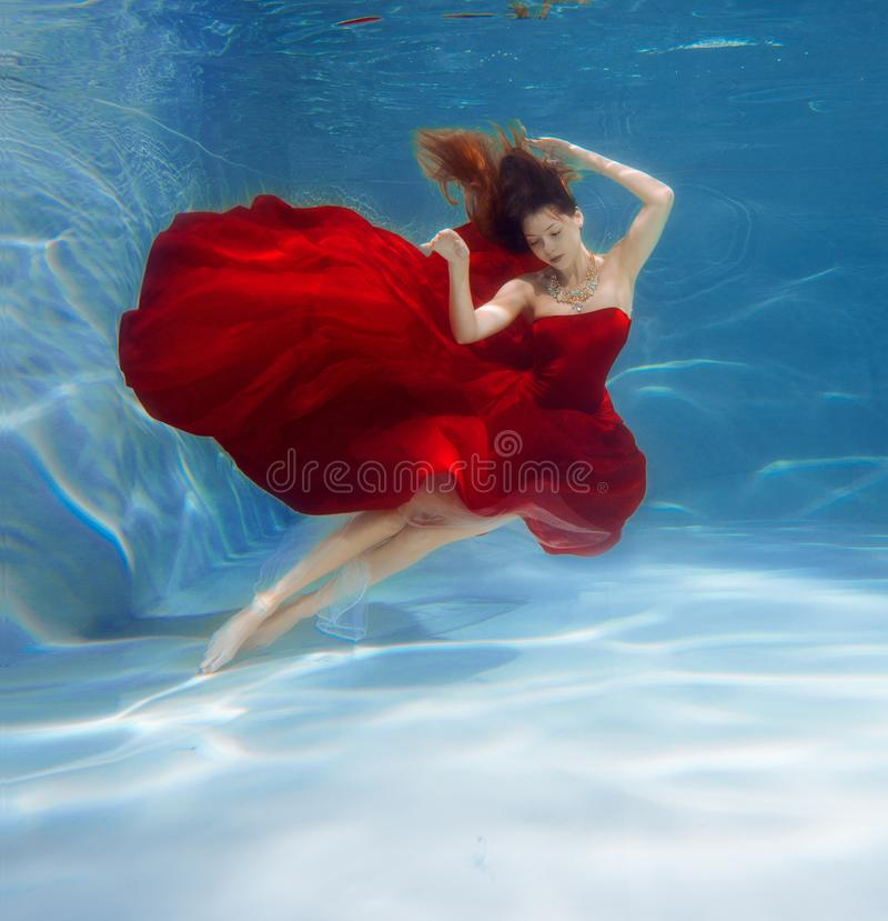 Girl mermaid. Underwater scene. A woman, a fashion model in the. Water in a beautiful dress swims like a fish royalty free stock photo