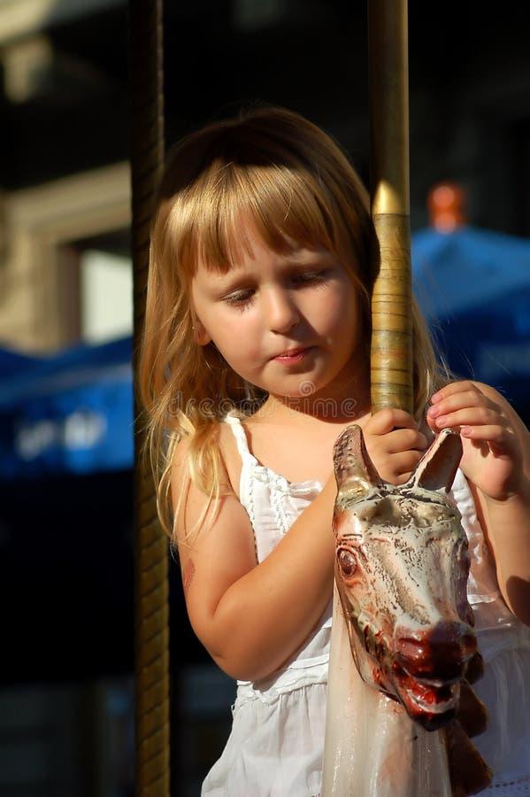 Girl on merry go around stock photo