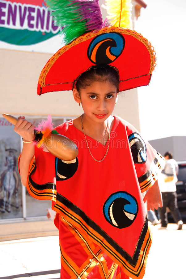 Girl in Mexican costume. A Latina young girl in bright red Mexican Azetec costume, a bright red hat with colorful feathers and a maraca on her right hand on stock images