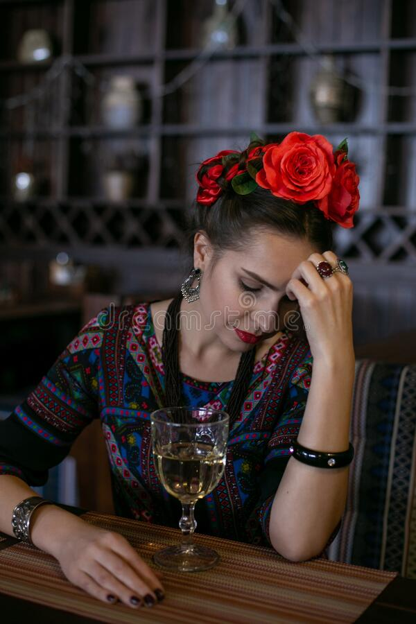 Vertical photo of a young woman in mexican national dress who is sitting at a table with a glass of wine. Girl in mexican national dress sitting at a table with royalty free stock photos