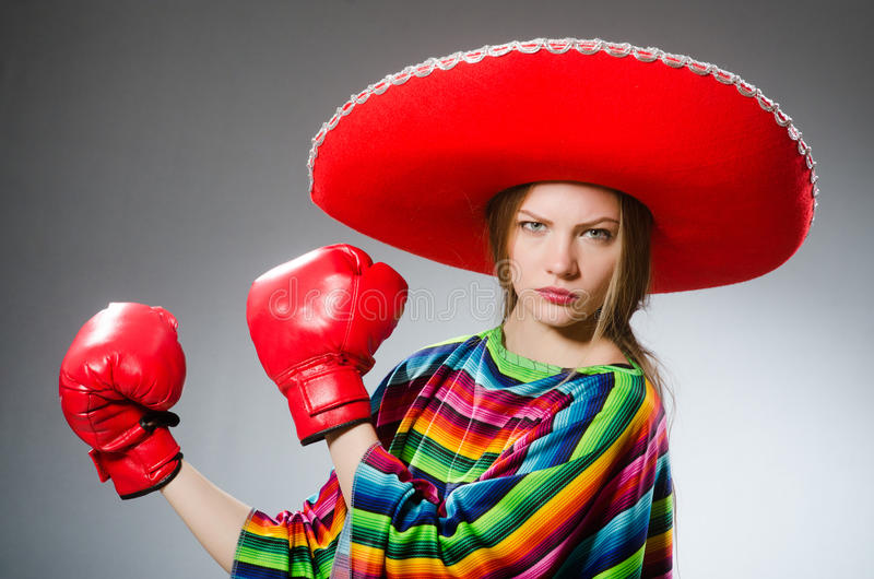 The girl in mexican vivid poncho and box gloves. Girl in mexican vivid poncho and box gloves against gray royalty free stock photography