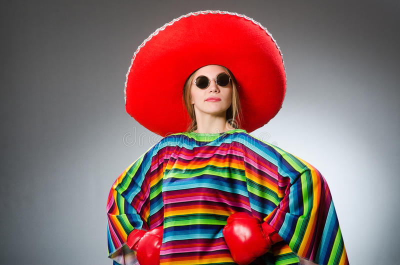 The girl in mexican vivid poncho and box gloves stock photo