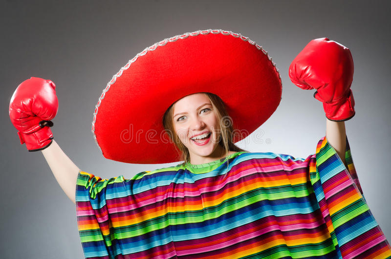 Girl in mexican vivid poncho and box gloves. The girl in mexican vivid poncho and box gloves against gray royalty free stock images
