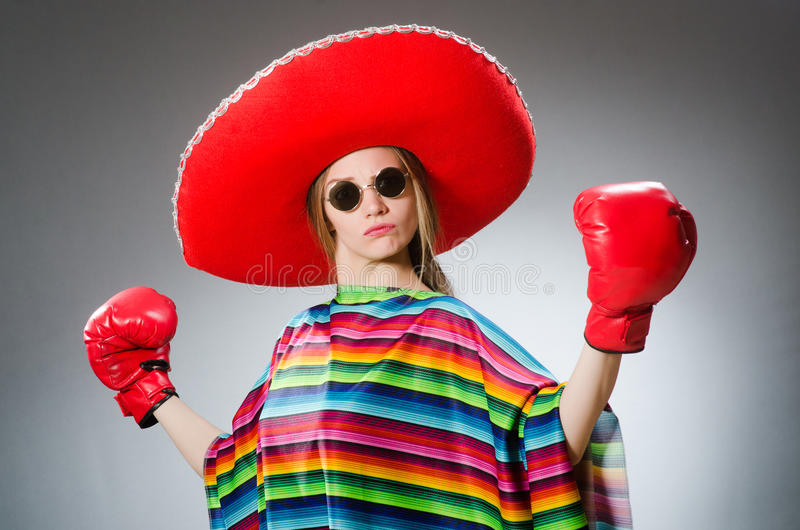 Girl in mexican vivid poncho and box gloves royalty free stock image