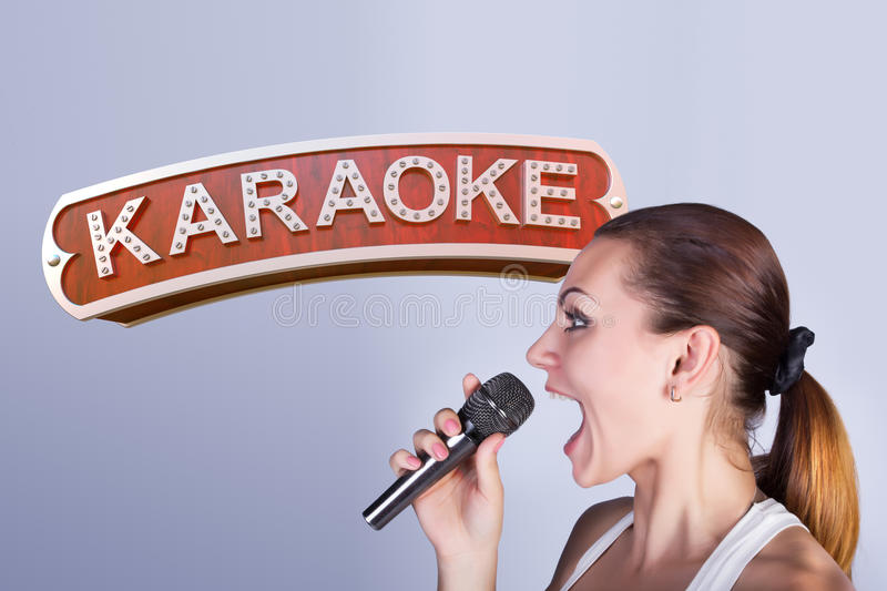 Girl with a microphone on the background of sign of karaoke. royalty free stock photography