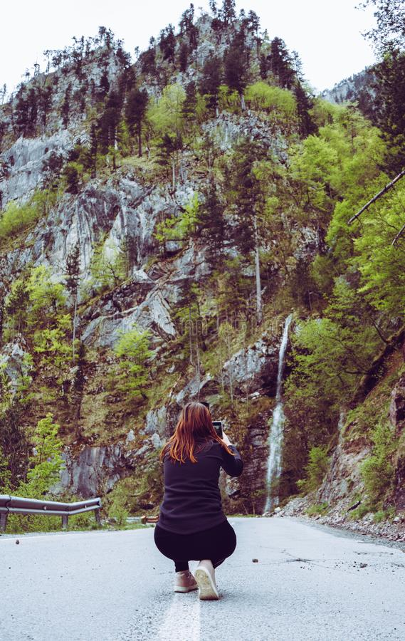 Girl in the middle of the road making picture to a Waterfall in Durmitor, Montenegro. Red head female taking picture with smart stock photo