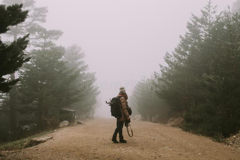 A girl in the middle of a road this stop looking towards the thick fog royalty free stock photo