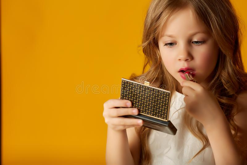 Girl with mirror rouging lips royalty free stock image