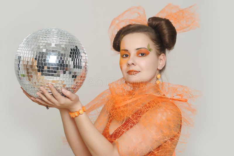 The girl with mirror sphere. The girl with an orange creative make-up with a mirror sphere stock photo