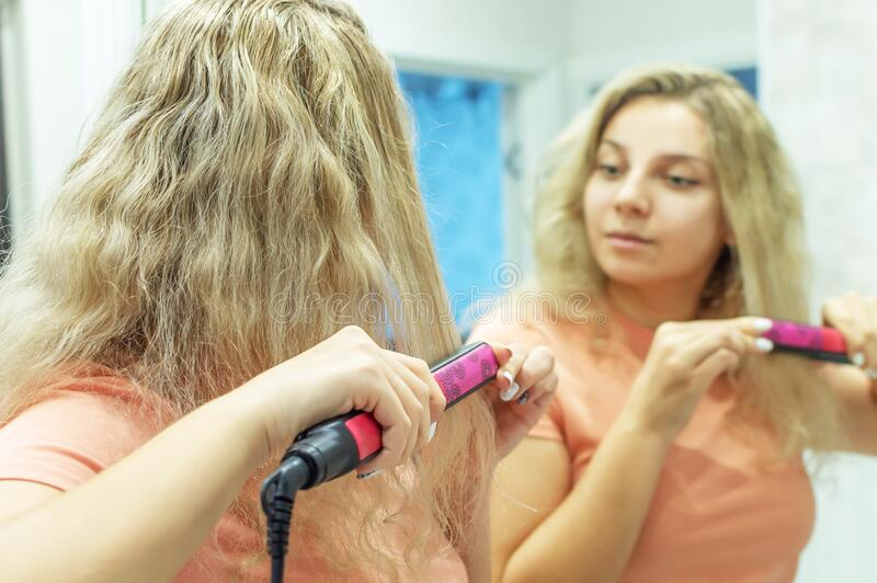 The girl at the mirror straightens curly hair with a hair straightener at home. Selective focus. Film grain royalty free stock photo