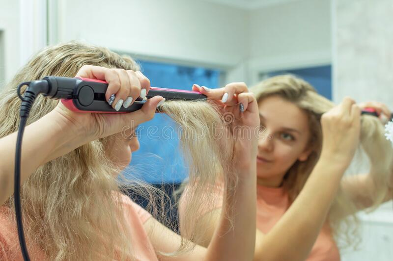The girl at the mirror straightens curly hair with a hair straightener at home. Selective focus. Film grain royalty free stock photos