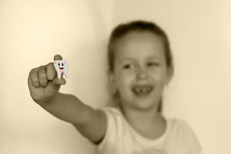 The girl with the missing tooth tooth shows a toy at arm`s length. Nn royalty free stock image