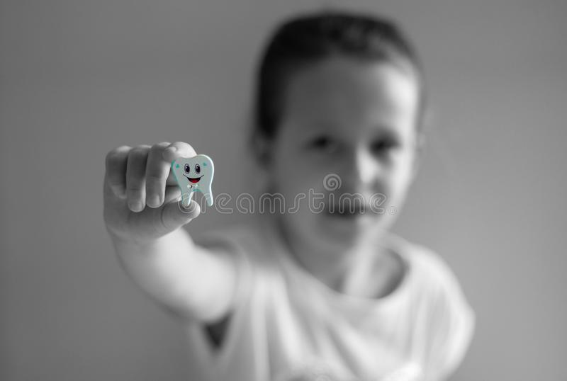 The girl with the missing tooth tooth shows a toy at arm`s length. Nn royalty free stock photo