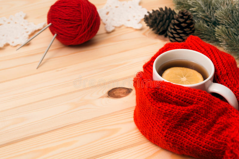 Girl in mittens gives a hot tea and knitted decoration royalty free stock photography