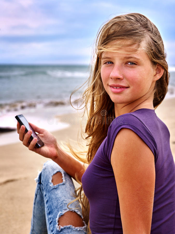 Girl with mobile phone sitting on sand near sea. stock images