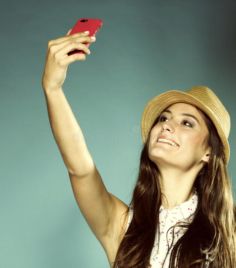 Girl with mobile phone taking photo of herself royalty free stock photo