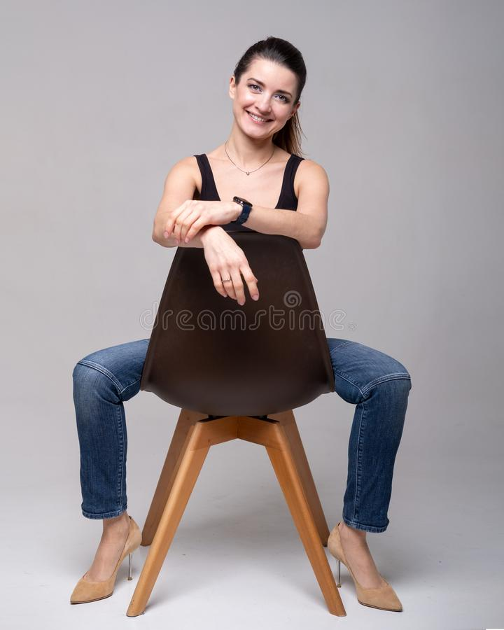 Girl model in black shirt and blue jeans with brown chair stock image