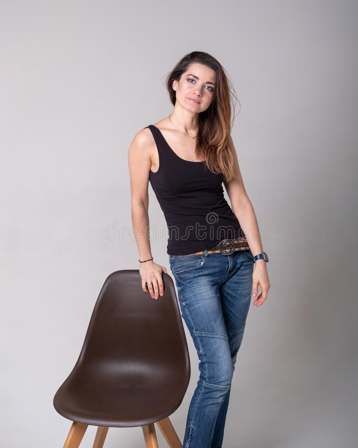 Girl model in black shirt with brown chair royalty free stock photography