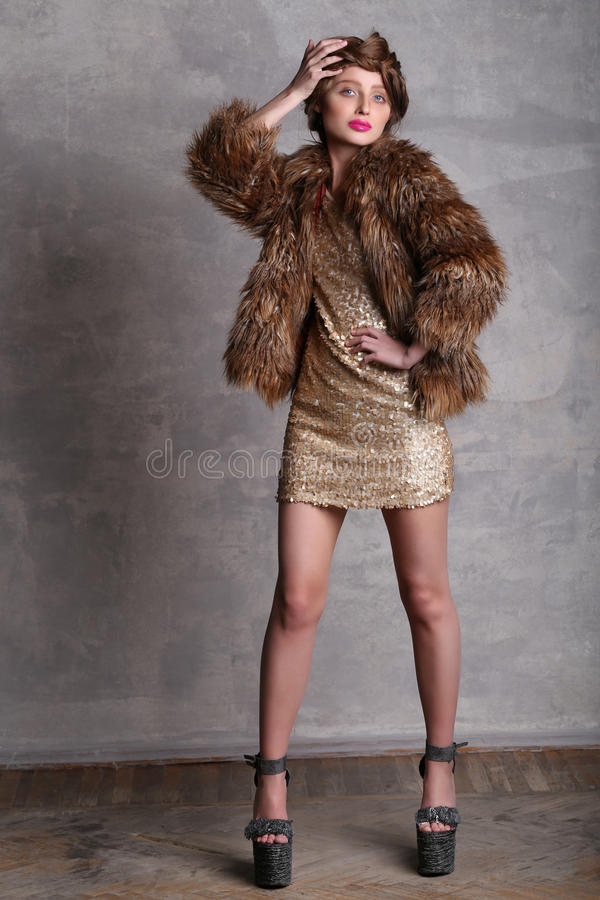 Girl model in gold dress and fur coat at full height royalty free stock photos