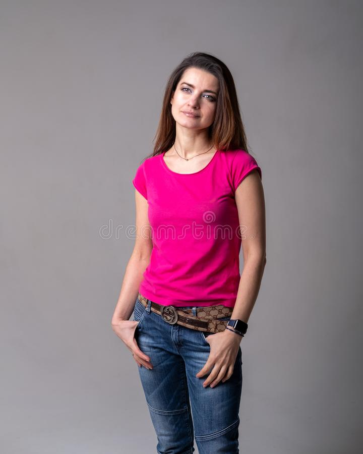 Girl model in pink shirt and blue jeans stock images