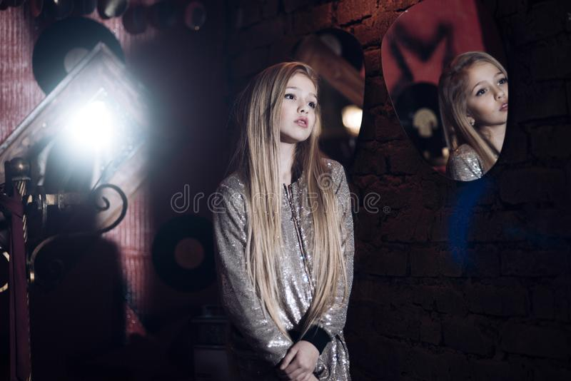 Girl model reflect in mirror in dressing room, fashion. Little child with long blond hair, hairstyle and beauty. Kid. Fashion trend and style. Baby beauty, hair royalty free stock photo